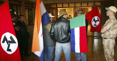 """In this June 11 2004, file photo, supporters of the Afrikaner Resistance Movement (AWB) display an old South African flag, second from left, an old Afrikaner """"Vierkleur"""" flag and swastika-like flags."""