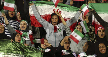 Iranian women cheer as they wave their country's flag after authorities in a rare move allowed a select group of women into Azadi stadium to watch a friendly soccer match between Iran and Bolivia, in Tehran, Iran.