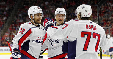 Washington Capitals' T.J. Oshie (77) celebrates his goal with teammate Chandler Stephenson (18) and Jakub Vrana (13) of Czech Republic during the first period of an NHL preseason hockey game against the Carolina Hurricanes, in Raleigh, N.C.