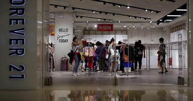 Women select clothing at an American fast fashion retailer Forever 21 which is offering clearance discounts at a shopping mall after it pulled out from China's market, in Beijing.