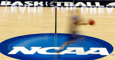 A player runs across the NCAA logo during practice at the NCAA tournament college basketball in Pittsburgh.