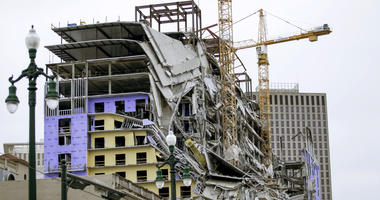 Debris hangs on the side of the building after a large portion of a hotel under construction suddenly collapsed in New Orleans on Saturday, Oct. 12, 2019.