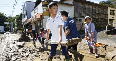 Students and residents scoop dirt as the town is flooded Typhoon Hagibis, in Marumori, Miyagi prefecture, northern Japan, Sunday, Oct. 13, 2019.