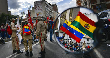 Reflected in a motorcycle side mirror, supporters of Venezuelan President Nicolas Maduro rally in support of former Bolivian President Evo Morales in Caracas, Venezuela, Monday, Nov. 11, 2019.