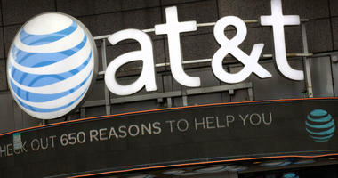 In this Monday, Oct. 24, 2016, file photo, the AT&T logo is positioned above one of its retail stores, in New York.