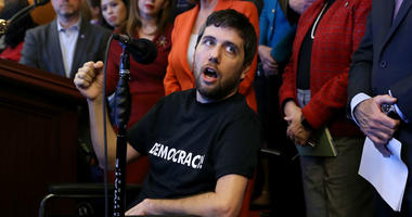 Ady Barkan, who lives with Amyotrophic Lateral Sclerosis, delivers remarks during a rally organized by House Minority Leader Nancy Pelosi (D-CA) in the Rayburn Room at the U.S. Capitol December 19, 2017 in Washington, DC.