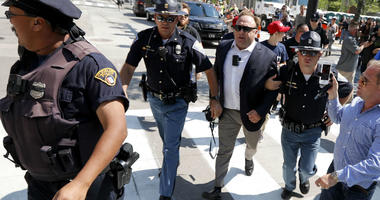In this Tuesday, July 19, 2016 file photo, Alex Jones, center right, is escorted by police out of a crowd of protesters outside the Republican convention in Cleveland.