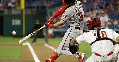 Washington Nationals' Bryce Harper, left, hits a two-run home run off Philadelphia Phillies starting pitcher Aaron Nola during the first inning of a baseball game, Wednesday, Sept. 12, 2018, in Philadelphia.