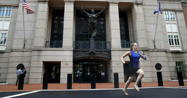 Cassie Semyon, 21, an intern for NBC News, runs from the courthouse with results as jury deliberations are announced in the trial of the former Donald Trump campaign chairman Paul Manafort in Alexandria, Va., Tuesday, Aug. 21, 2018.