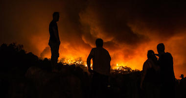 People stand next to the fire before being evacuated at the village of Monchique, in southern Portugal's Algarve region, Sunday, Aug. 5 2018.