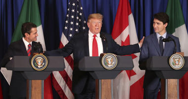 President Donald Trump, center, reaches out to Mexico's President Enrique Pena Nieto, left, and Canada's Prime Minister Justin Trudeau as they prepare to sign a new United States-Mexico-Canada Agreement that is replacing the NAFTA trade deal.