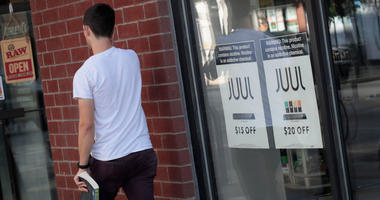 Signs in the window of the Smoke Depot advertise electronic cigarettes and pods by Juul, the nation's largest maker of e-cigarette products, on September 13, 2018 in Chicago, Illinois.