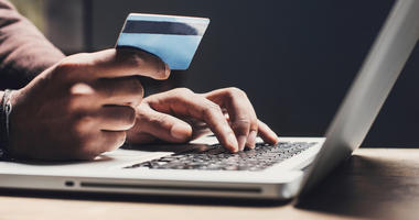 Man shopping online using laptop computer and credit card - stock photo