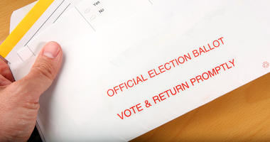 Man opening vote by mail ballot