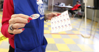 "Poll worker hands out an ""I voted"" sticker."