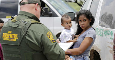 In this June 25, 2018, file photo, a mother migrating from Honduras holds her 1-year-old child as surrendering to U.S. Border Patrol agents after illegally crossing the border near McAllen, Texas.