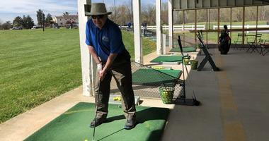 A veteran takes a swing during the First Swing golf clinic for amputees and people with disabilities.
