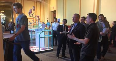Mayor Jim Kenney looks on as a group of startup entrepreneurs demonstrate what they've been working on.