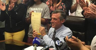 Gov. John Carney signed the bill to raise the legal age from 18 to 21 to purchase cigarettes and tobacco products in Delaware.