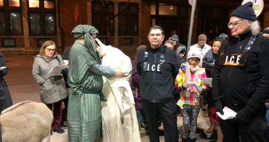 Mary and Joseph knock on doors in the neighborhood while mock ICE agents confront them.