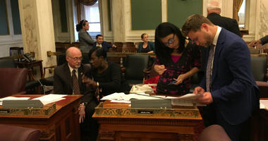 Council members Bill Greenlee and Cherelle Parker exchange thoughts on the budget while Coucilmember Helen Gym looks over the numbers with an aide.