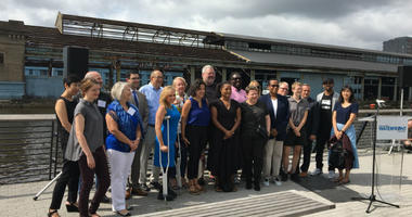 City representatives and artists pose for a photo on Race Street Pier, overlooking Cherry Street Pier, which will open Oct. 12.
