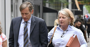 Jeffrey Bizzack, left, arrives at federal court with a member of his defense team, Wednesday July 24, 2019, in Boston where he is expected to plead guilty to charges for allegedly paying to get his son into the University of Southern California.