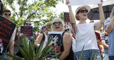 People at the Keep Families Together rally, including Marsha Gore, right, and Claudia Short, cheer as the son of Holocaust survivors speaks about the importance of offering asylum in the South Plaza of the Oklahoma State Capitol Building in Oklahoma City.