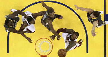 Cleveland Cavaliers forward LeBron James, bottom, shoots against the Golden State Warriors during the second half of Game 2 of basketball's NBA Finals in Oakland, Calif., Sunday, June 3, 2018.