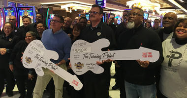 From left: Joe Lupo on, dealer Steven Scheck and Rev. Collins Days hold guitars representing a $16,400 donation.