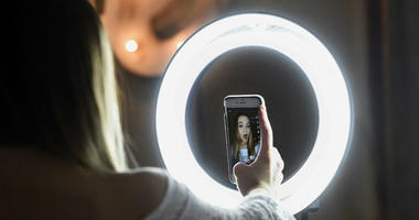 In this Feb. 28, 2018 photo, Matty Nev Luby holds up her phone in front of a ring light she uses to lip-sync with the smartphone app Musical.ly, in Wethersfield, Conn.