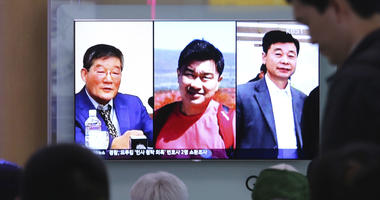 In this May 3, 2018 photo, people watch a TV news report on screen, showing portraits of three Americans, Kim Dong Chul, left, Tony Kim and Kim Hak Song, right, detained in the North Korea, at the Seoul Railway Station in Seoul, South Korea