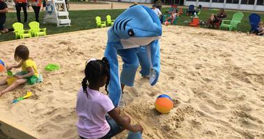 A temporary beach on North Broad Street has a shark mascot.