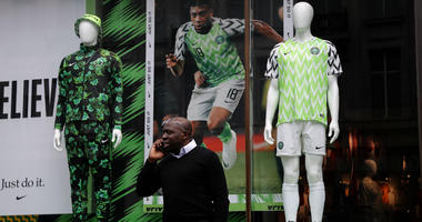a man stands in front of a Nigerian national soccer team jersey is on display at a shop in London