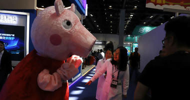 a woman reacts to a Peppa Pig mascot