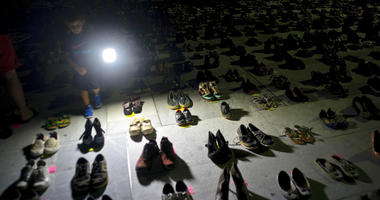 In this June 1, 2018 file photo, a child shines a light on hundreds of shoes at a memorial for those killed by Hurricane Maria, in front of the Puerto Rico Capitol in San Juan.
