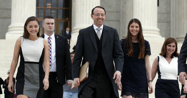 In this April 23, 2018 file photo, Deputy Attorney General Rod J. Rosenstein departs the Supreme Court in Washington, with his family, after arguing his first case before the court.