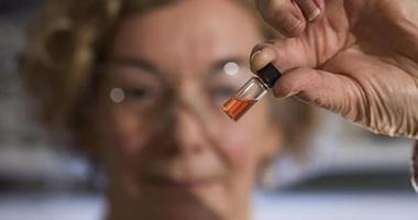 ANU Biogeochemistry Lab Manager Janet Hope holds a vial containing the world's oldest intact pigments.