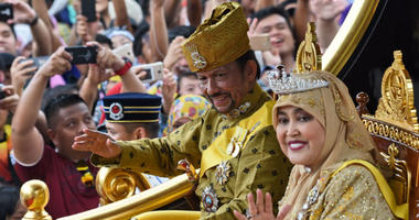 Brunei's Sultan Hassanal Bolkiah and Queen Saleha ride in a royal chariot during a procession to mark his golden jubilee of accession to the throne in Bandar Seri Begawan.