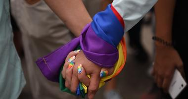 A couple hold hands wrapped in a rainbow flag during a pride march in Marikina City, east of Manila on June 30, 2018.