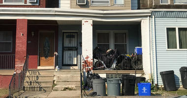 A neighbor on Carroll Street in SW Philadelphia says the house with the white door is the site of a deadly shooting.