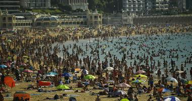 People crowd La Concha beach in the basque city of San Sebastian, northern Spain, Friday, Aug. 3, 2018.