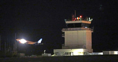 A plane flies past a control tower at Sea-Tac International Airport Friday evening, Aug. 10, 2018, in SeaTac, Wash.