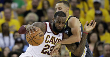 Golden State Warriors guard Stephen Curry, right, shoots against Cleveland Cavaliers forward Kevin Love (0)