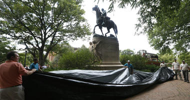 In this Aug. 23, 2017, file photo, city workers prepare to drape a tarp over the statue of Confederate General Stonewall Jackson in Justice park in Charlottesville, Va.