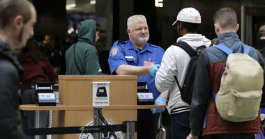 A TSA worker checks hands an identification card back to a traveler, Friday, Jan. 25, 2019, at Seattle-Tacoma International Airport in Seattle.
