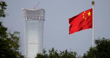 In this Thursday, June 14, 2018, file photo, a Chinese national flag at Tiananmen Square flutters against the capital city tallest skyscraper China Zun Tower under construction at the Central Business District in Beijing.
