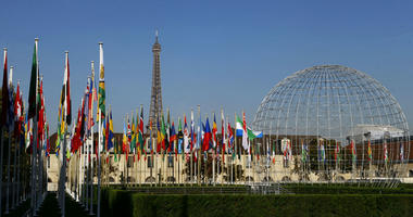 In this Tuesday Oct. 31, 2017 file picture, the Eiffel Tower, country flags and the Dome are seen from the garden of the UNESCO headquarters in Paris, France.
