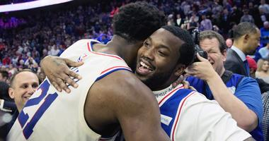 Philadelphia 76ers center Joel Embiid hugs rapper Meek Mill after a victory against the Miami Heat.