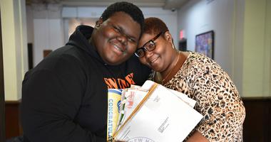 Dylan Chidick of Jersey City, NJ and his mother Khadine Phillip hold his seventeen acceptance letters from college.
